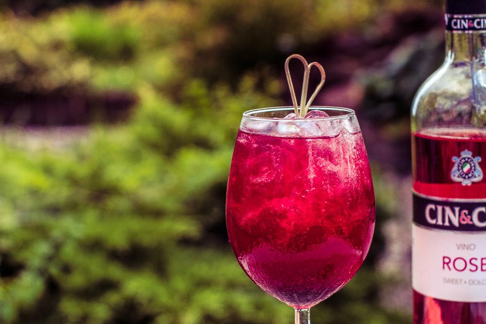 Orzeźwiający kobiecy drink z różowym winem i jagodami.